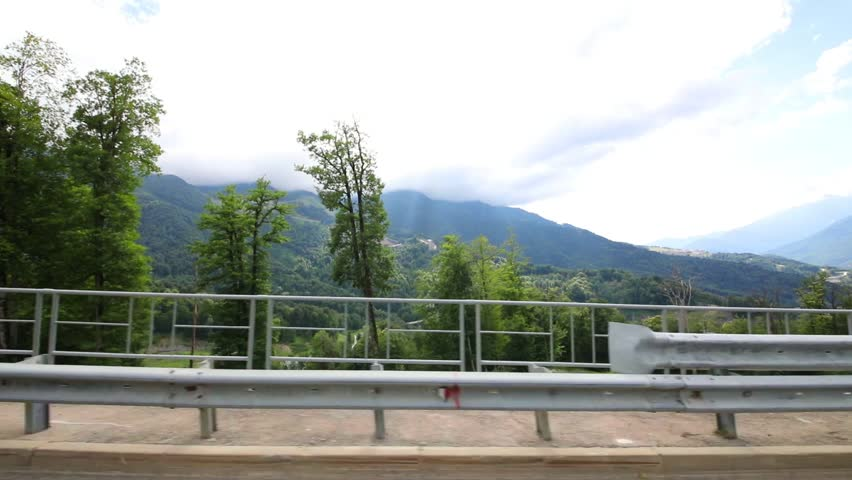 Moving in car on road among foggy mountains at summer, Sochi, Russia, side view