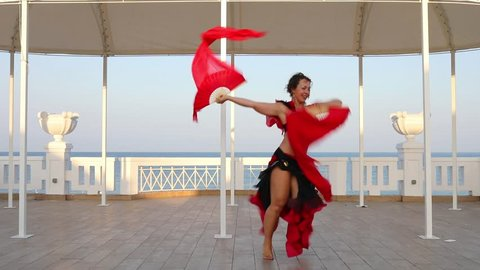 Woman dances belly dance in flamenco costume with fans at stage near blue sea