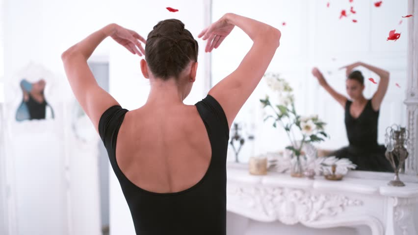 Graceful ballerina throwing red petals in slow motion