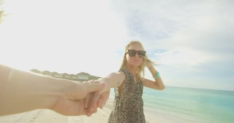 POV Footage. Beautiful Woman Holding Hands With Boyfriend Leads Him on the Beach Towards the Sea. White Sand, Palm Trees and Green Water. Paradise Island Romantic Vacation. Shot on RED Epic 4K UHD.