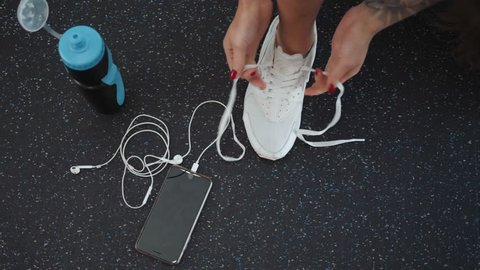 Top View Young woman tying shoelaces on floor, top view. Ready for gym workout phone headphones cell mobile water girl prepare