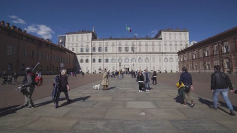 TURIN, ITALY - CIRCA MAY 201T: Castle square (piazza castello) and Royal Palace (Palazzo Reale) with people visiting in a blue sunny day