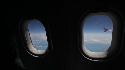 View of the blue sky and clouds through the window of the aircraft, Close up Airplane window with airplane wing, Traveling concept.