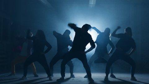 Teens taking part in dancing battle outside.