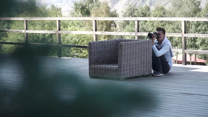 Photographer takes a photo on his camera sitting on the porch behind the chair | Shutterstock HD Video #1009358930