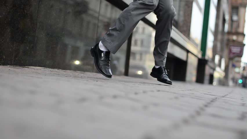 Man's legs make fast fun dance movements at asphalt in summer day. Camera on ground. Break dance.