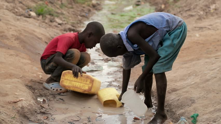 UGANDA, GULU - 15 February 2017: Children fetching dirty drinking water for both domestic and animal use. African children using a large bottle to fill water from a dirty water source