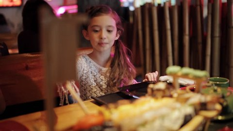 Cute little kid girl in restaurant funny try eating sushi with chinese chopsticks unsuccessful attempt