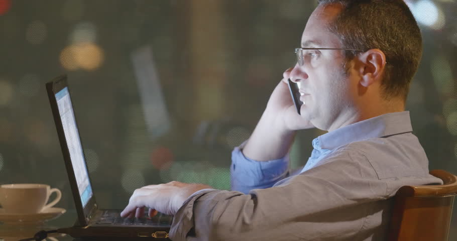 Man on phone reviews the business results on computer at the office | Shutterstock HD Video #1009405190