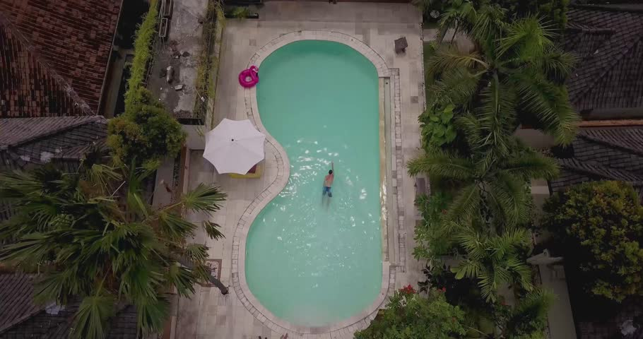 Athletic male swimming in a figure 8 pool on a sunny day in Bali with nice blue crystal clear water surrounded by palms trees by aerial drone 4k footage.