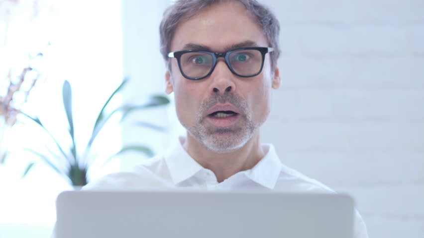 Close Up of Shocked Middle Aged Man Wondering while Working on Laptop | Shutterstock HD Video #1009437710
