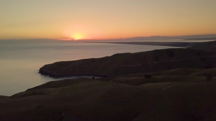 Coast of New Zealand shot by drone during sunrise or sunset in autumn season. Scenic and pristine nature | Shutterstock HD Video #1009448390
