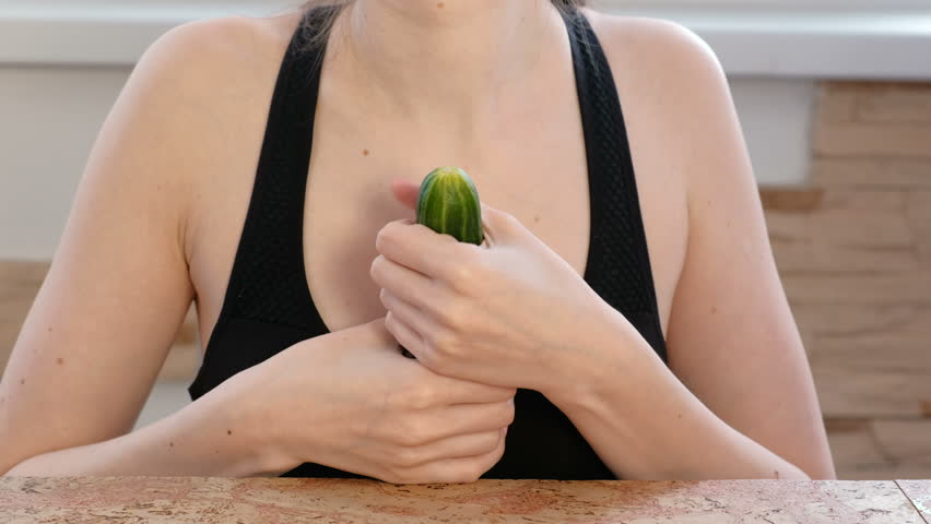 Woman hands holding cucumber and play with it. Safe sex concept.