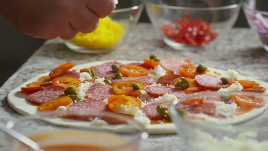 Close up shot of restaurant chef adding red onion circles to pizza topped with grated cheese, tomatoes, salami, and capers