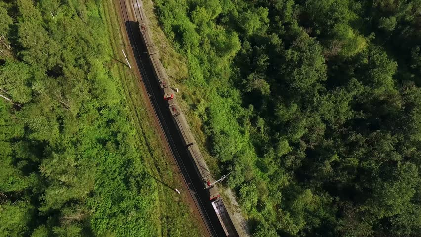 Freight train carries an electric locomotive by two-sided winding railways with railroad crossing  in the Ural Mountains - Aerial Photography, top view | Shutterstock HD Video #1009466420