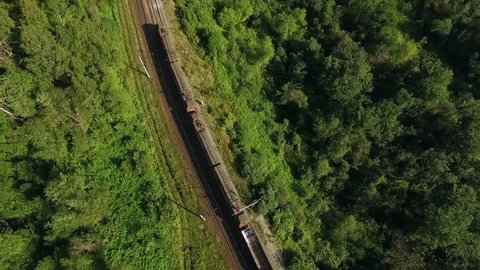 Freight train carries an electric locomotive by two-sided winding railways with railroad crossing  in the Ural Mountains - Aerial Photography, top view