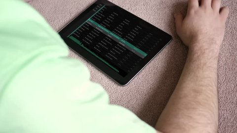 A man listens to a generic fake app playlist on his tablet - Dubstep Version
