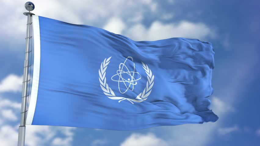 International Atomic Energy Agency (IAEA) flag waving against clear blue sky, close up, isolated with clipping path mask luma channel, perfect for film, news, composition