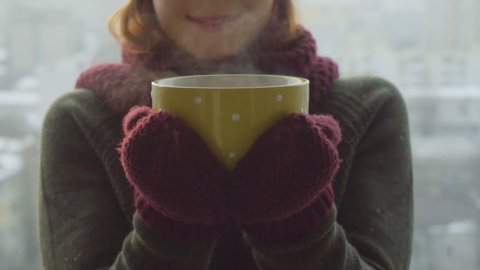 Woman Drinks Hot Tea or Coffee From yellow Cup on Winter Morning
