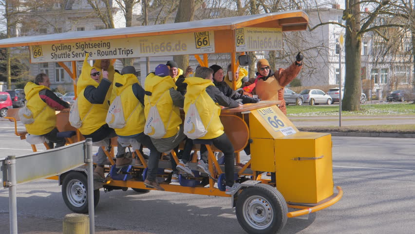 LUBECK, GERMANY - MARCH 30, 2018: Happy germans riding on a fun car bike and enjoying the beer and nice day