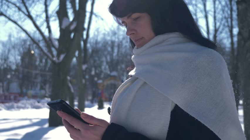 4K 60p Happy Smiling Beautiful Woman Using Smart Phone. Sunny Day In Snow Covered City Park. Winter Holidays | Shutterstock HD Video #1009505540