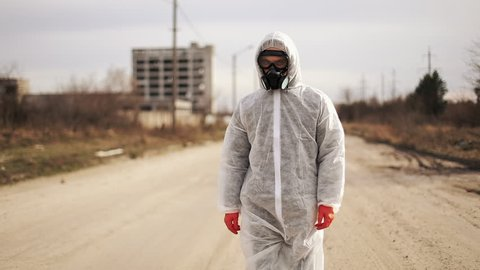 Virologist man in protective costume and respirator gas mask walk in a deserted city at the industrial factory background