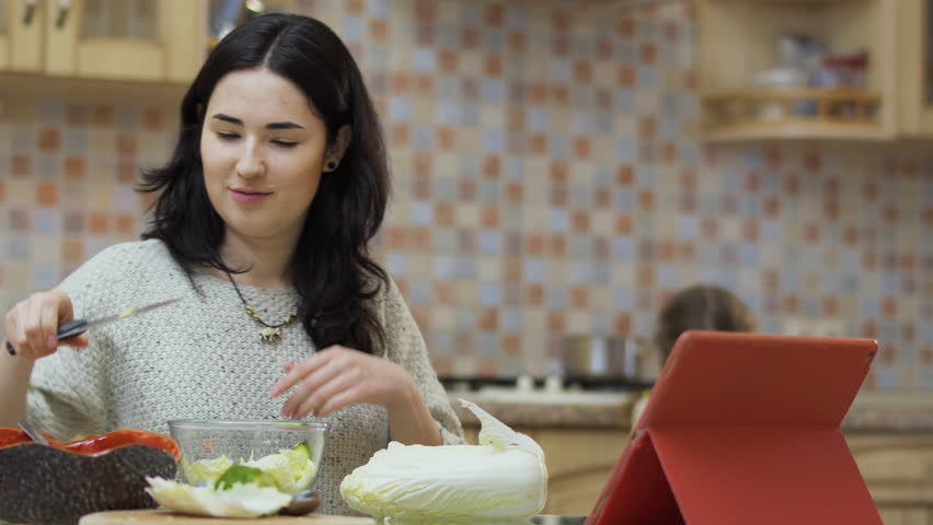Little girl brings a pan to mother to put salad inside it | Shutterstock HD Video #1009514960