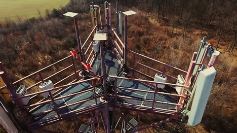 Close up video of Base transceiver station tower (BTS) on green meadow and forest from above (with drone). Bts tower on spring.