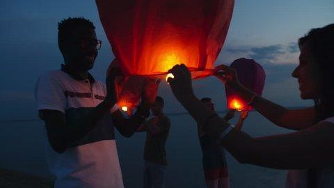 Medium shot of group of friends releasing sky lanterns on beach at dusk and celebrating something