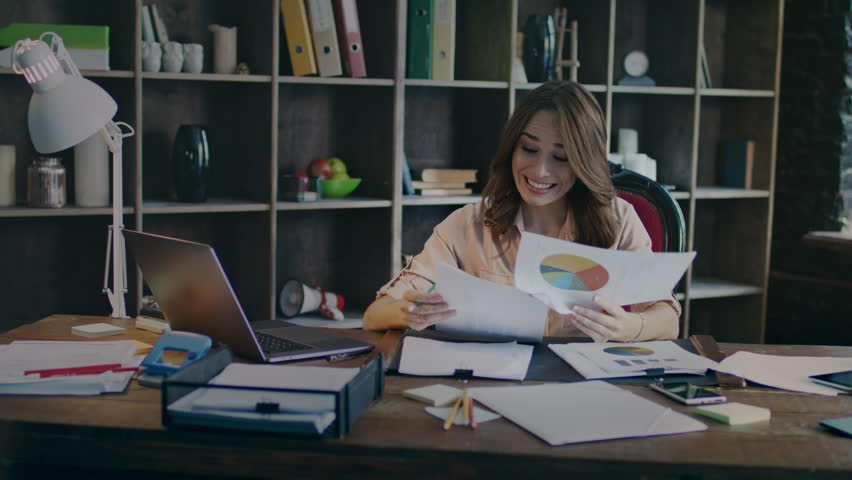 Smiling businesswoman reading documents with good statistics graph at desk. Growth business concept. Successful business plan is working. Happy employee looking business graph