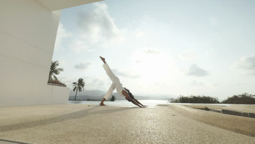 Healthy woman practicing Bhujangasana in snake pose and cobra pose on outdoor terrace with sea landscape. Fitness woman training Parvatasana in mountain pose #1009525550