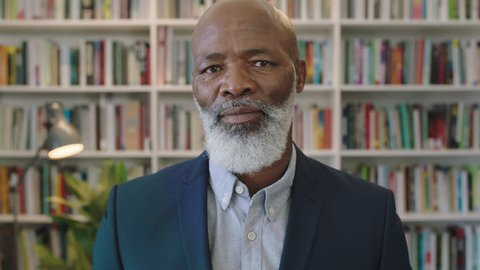 close up portrait of mature african american businessman with beard smiling confident enjoying successful career milestone professional senior black male wearing suit in library