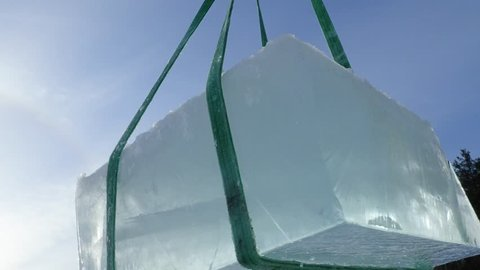 Giant ice cube swaying in the air after being lifted up from an ice hole with slings.