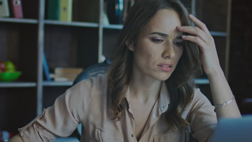 Worried business woman face looking at laptop in office. Close up of upset businesswoman thinking about mistakes in work. Portrait of sad girl looking laptop. Depressed employee working on laptop