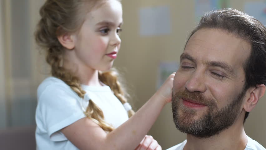 Caring daughter combing father hair and kissing cheek, family love, parenthood