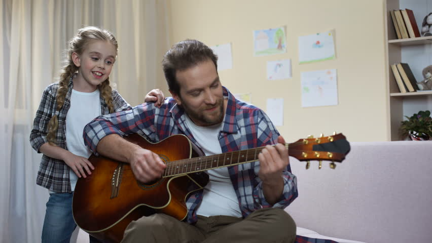 Talented girl singing while father playing guitar, home concert, musical hobby #1009578620