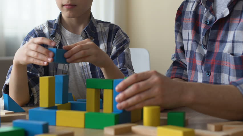 Teenager playing with cubes, volunteer looking after him