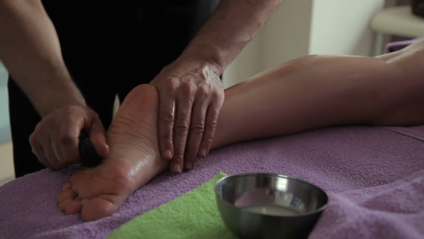 Masseur Makes Foot Massage With Hot Stones In Spa Center Man Holds Volcanic Stone In Hand And Rubs Vigorously Delicate Skin Of Clients Legs Which Lies On