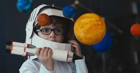 CU Cute little boy wearing cardboard astronaut helmet flying toy rocket through planets, exploring deep space. 4K UHD 60 FPS SLOW MO