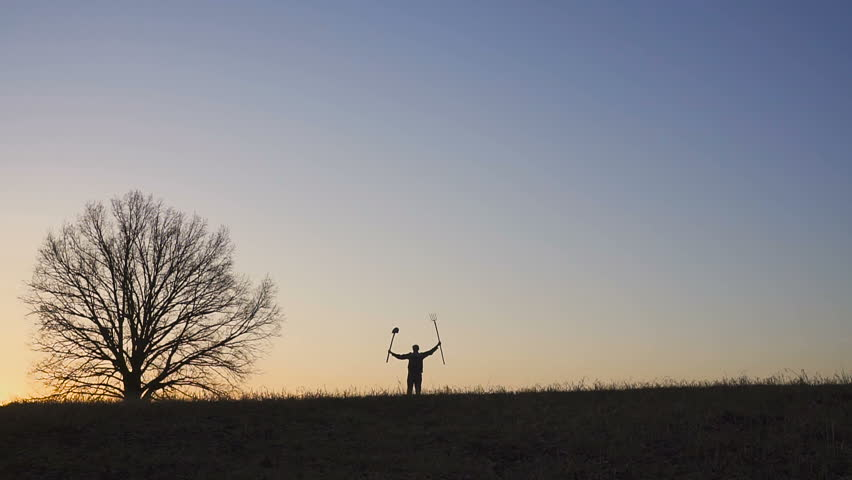 A satisfied farmer waving his hands with a shovel and pitchforks. Silhouette of a sunset or sunrise in field.