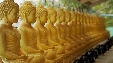 Golden Buddha statues stand in row on summer terrace against background of rustling green trees in windy weather, symbols of faith create tranquil atmosphere. Concept: asian culture, traditional