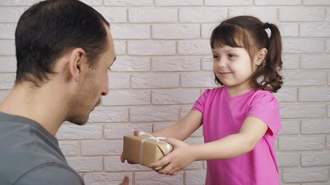 The child gives a gift to the father. Father's Day.