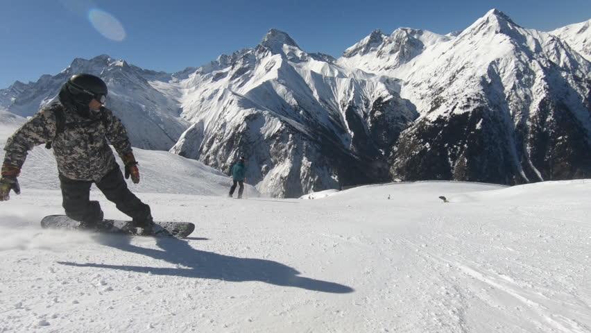 Snowboarding on mountains at sun