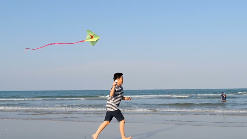 Boy running with kite at beach, slow motion  | Shutterstock HD Video #1009674560