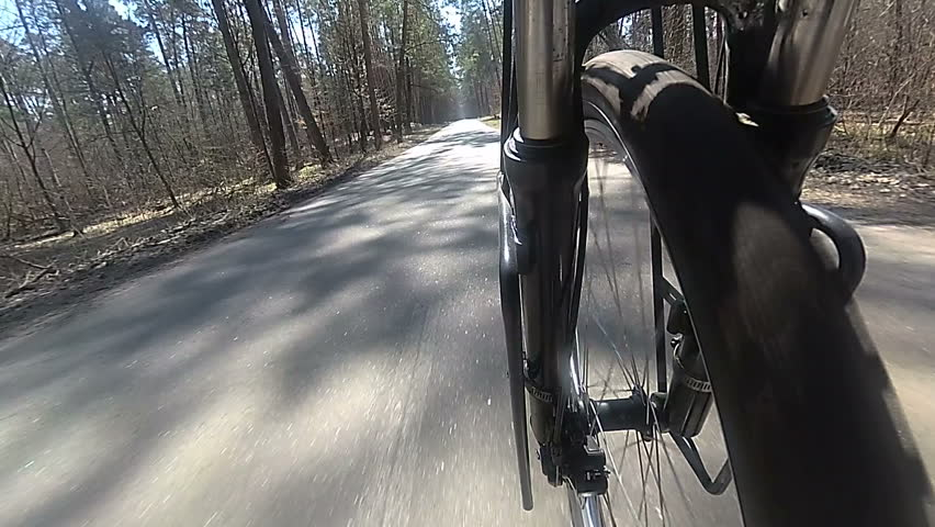 Wheel of  bicycle  with tyre goes on asphalt  road. Spring slow motion  | Shutterstock HD Video #1009674920