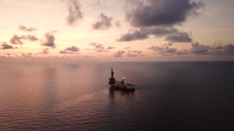 Aerial view from a drone of a tender assisted drilling rig in the middle of the ocean view during sunset