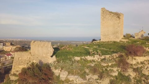 Medieval vintage castle with an old damaged defensive tower and wall near the coastline of the Mediterranean sea. Aerial view.