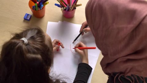 Young beautiful mother in hijab, small daughter paints with colored pencils, paints, children's coloring, family idyll concept, close up, top shot 50 fps