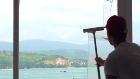 Clean employee using squeegee for cleaning window glass with panoramic sea view. Housekeeper cleaning window with view sea port in luxury resort hotel