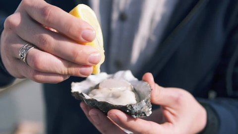 Close-up shot of a young guy with a stylized mustache pouring lemon juice on the open oysters and eat it at the street. Delicious seafood in hand, Dynamic Slow motion
